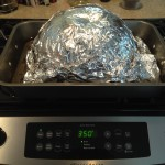 Pumpkin half in baking tin wrapped in foil